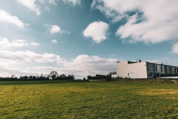 Weitwinkelaufnahme eines gebäudes umgeben von grüner landschaft