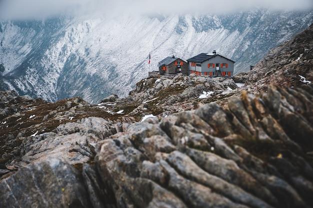 Weitwinkelaufnahme eines hauses isoliert auf den schneebedeckten bergen in capanna cadlino