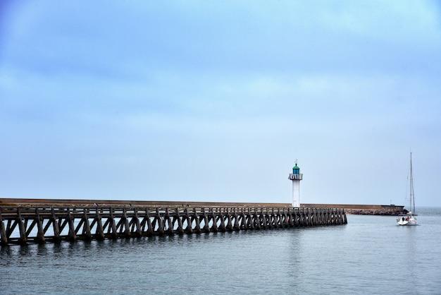 Weitwinkelaufnahme eines langen piers im meer unter dem schönen blauen himmel