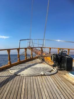 Weitwinkelaufnahme eines seils, das in einer kreisförmigen position auf einem schiff über dem ozean unter einem blauen himmel gedreht ist
