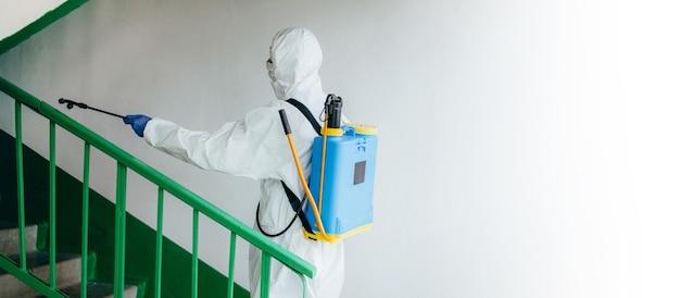 Weitwinkelaufnahme. sanitärfachmann im schutzanzug desinfiziert einen wohnblock im treppenhaus. maßnahmen zur vorbeugung von coronaviren in wohngebieten. neue normal- und stopp-covid-19-ausbreitung.