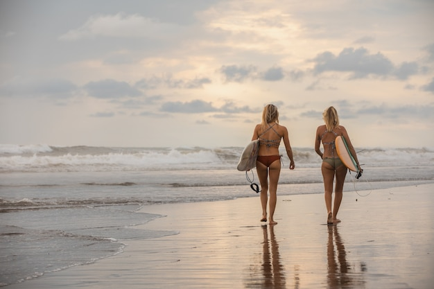 Weitwinkelaufnahme von zwei mädchen mit surfbrettern, die auf dem strand gehen