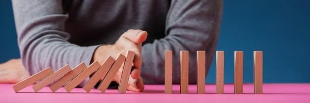 Weitwinkelbild eines mannes, der verhindert, dass dominosteine auf rosa oberfläche in einem konzeptuellen bild zusammenbrechen.