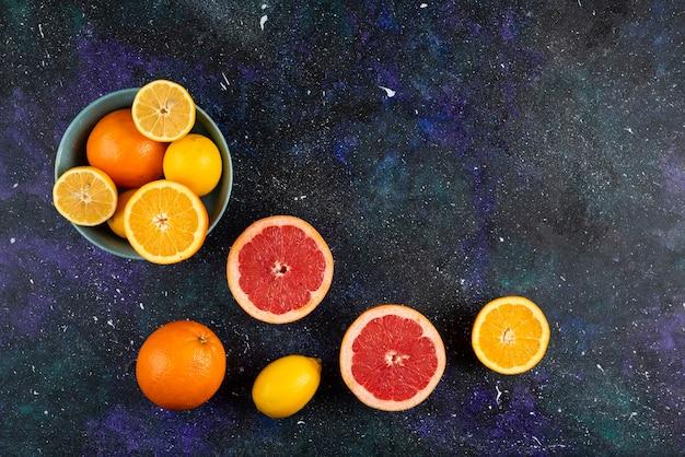 Weitwinkelfoto eines haufens von zitrusfrüchten ganz oder in scheiben geschnitten.