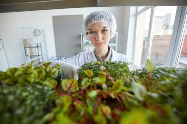 Weitwinkelporträt der lächelnden wissenschaftlerin, die pflanzenproben während der arbeit im biotechnologielabor, kopierraum untersucht