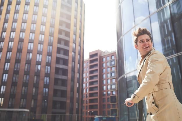 Weitwinkelporträt des freudigen jungen mannes, der trenchcoat trägt, der zurück schaut, während er zügig über schuss mit städtischen stadtgebäuden im hintergrund, kopienraum geht