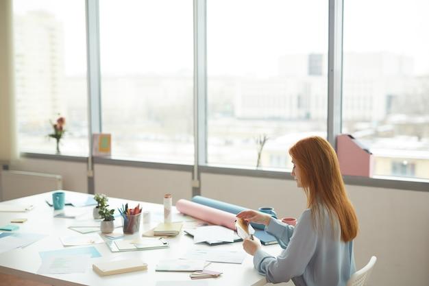 Weitwinkelporträt des rothaarigen weiblichen designers, der farbmuster hält, während am arbeitsplatz durch fenster sitzen, raum kopieren