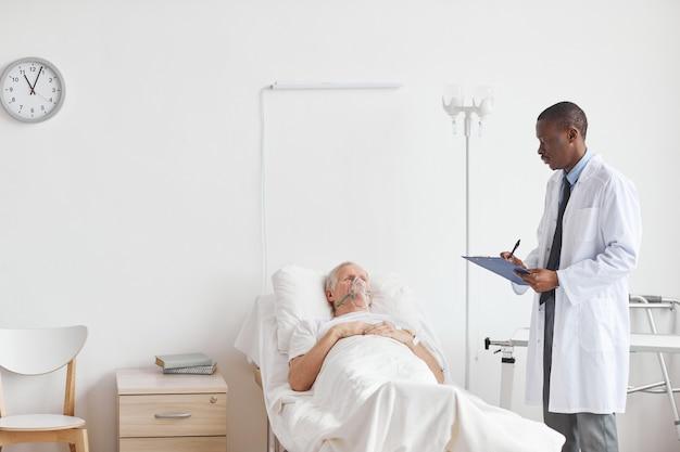 Weitwinkelporträt eines afroamerikanischen arztes, der bei einem älteren mann steht, der im krankenhausbett mit sauerstoffergänzungsmaske liegt, kopierraum