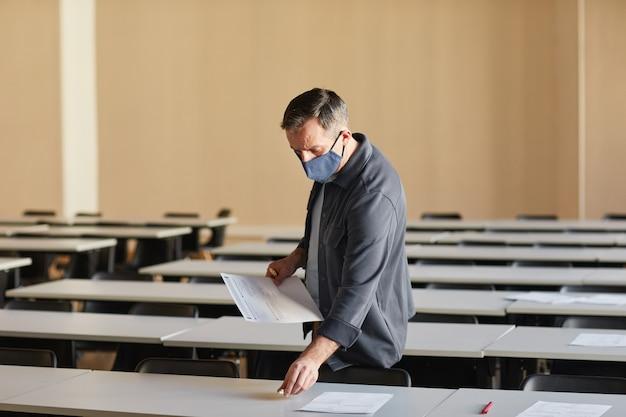 Weitwinkelporträt eines reifen college-professors mit maske beim auslegen von prüfungsunterlagen in der von sonnenlicht beleuchteten schulaula, kopierraum