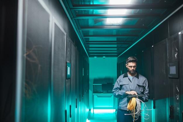 Weitwinkelporträt eines reifen netzwerkingenieurs mit digitalem tablet im serverraum während wartungsarbeiten im rechenzentrum, kopierraum
