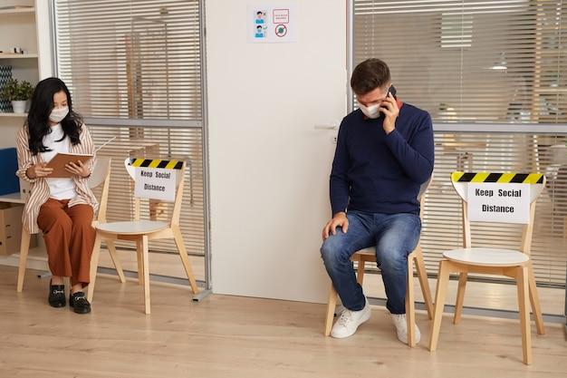 Weitwinkelporträt von jungen leuten, die masken tragen, während sie in der schlange im büro mit zeichen der sozialen distanz warten warten, raum kopieren