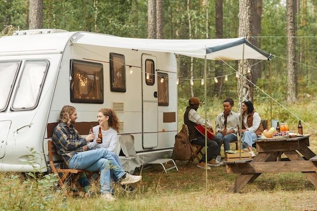 Weitwinkelsicht auf eine gruppe junger leute, die sich im herbst mit dem wohnmobil im freien entspannen