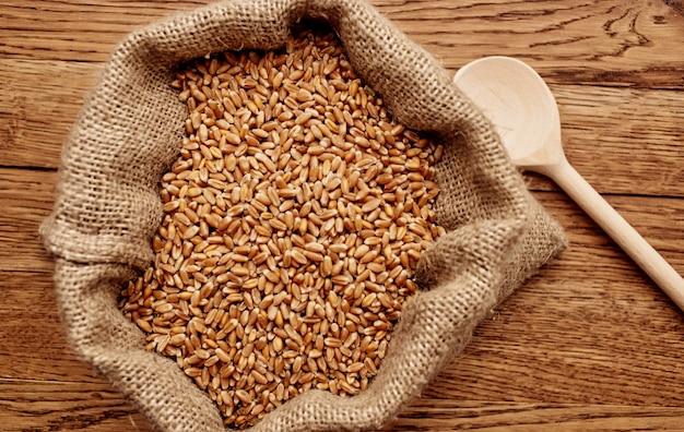 Weizen besprengte auf einer hölzernen tischbeschaffenheitsbild-getreide-nahrungsmittelzubereitung