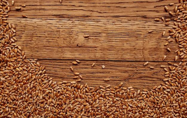 Weizen besprengte auf einer hölzernen tischbeschaffenheitshintergrund-getreidefutterzubereitung.
