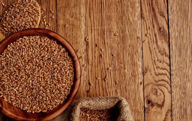 Weizen, der auf eine hölzerne tischbeschaffenheitsbild-getreide-nahrungsmittelzubereitung gestreut wird. hochwertiges foto