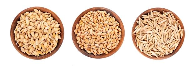 Weizen-, hafer- und gerstenkörner in der holzschale, lokalisiert auf weiß.