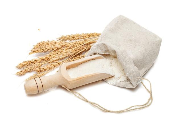 Weizen in beutel und schaufel isoliert auf weißem tisch
