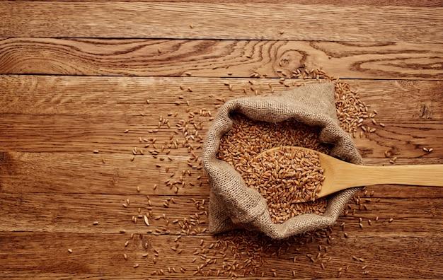 Weizen in einer tasche hintergrundbild holztisch getreide produkte draufsicht