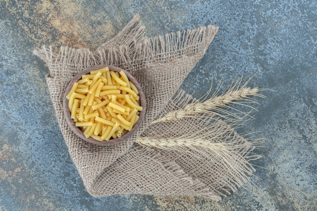 Weizen mit einer schüssel nudeln auf dem handtuch, auf der marmoroberfläche.