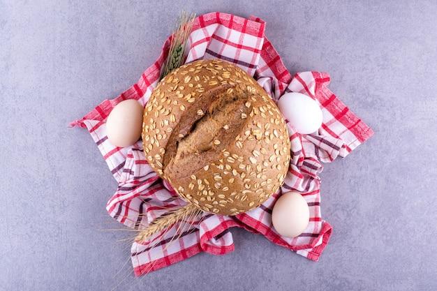 Weizen pirscht eier und einen laib brot auf einem handtuch auf marmoroberfläche