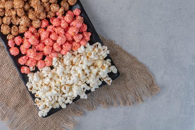 Weizen und reis auf einem holzbrett auf marmor gestapelt.
