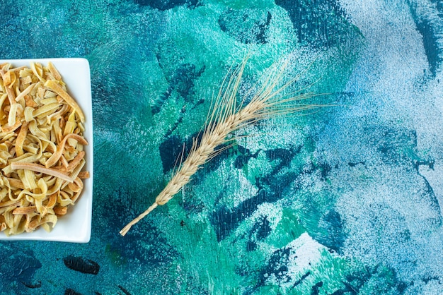 Weizenähre und eine schüssel hausgemachte nudeln auf dem blauen tisch.