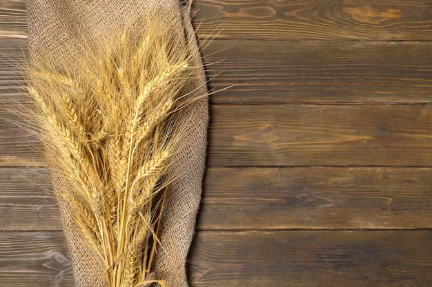 Weizenähren auf dem holztischhintergrund