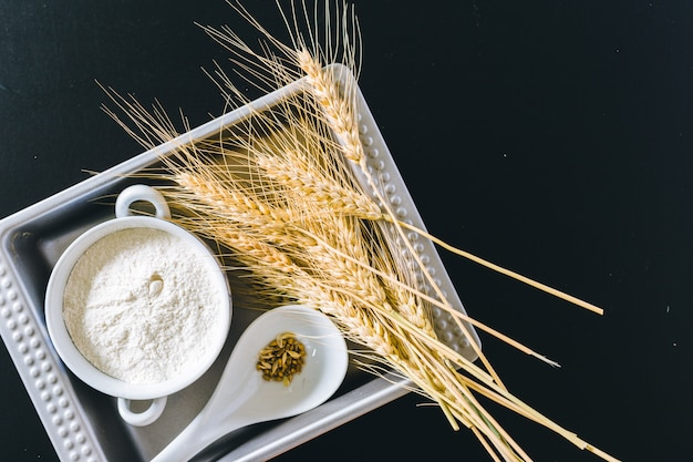 Weizenähren und mehl auf schwarzem hintergrund