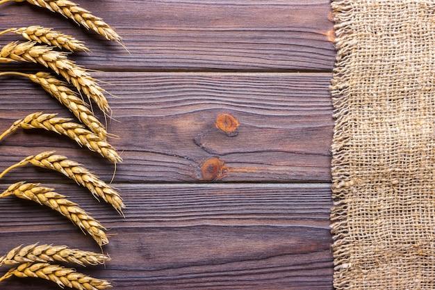 Weizenähren und stoff auf hölzernen hintergrund