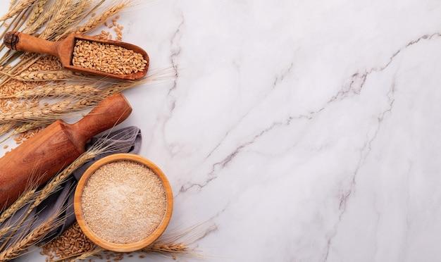 Weizenähren und weizenkörner auf marmorhintergrund. draufsicht und kopierbereich