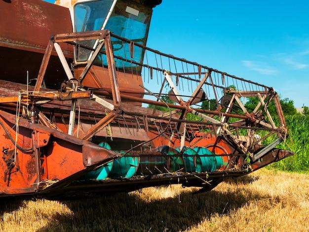 Weizenernte im sommer. roter mähdrescher, der im feld arbeitet. landwirtschaftliche maschinenerntemaschine der goldenen reifen weizenernte auf dem feld.