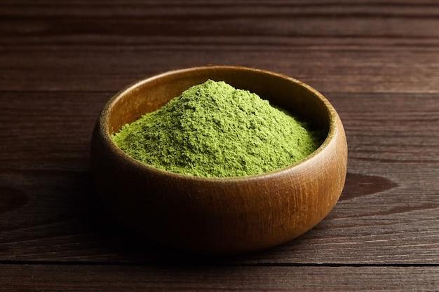 Weizengras- oder gerstengraspulver in der holzschale auf dunklem hintergrund. natürliches nahrungsergänzungsmittel.