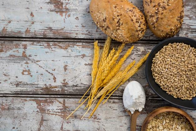 Weizenkörner mit brötchen, hafer und löffel voller mehl