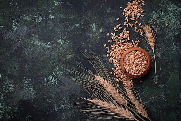 Weizenkörner und ährchen auf rostigem hintergrund.