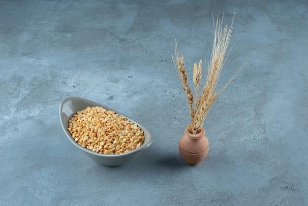 Weizenkörner und maisbohnen auf blauem hintergrund. foto in hoher qualität