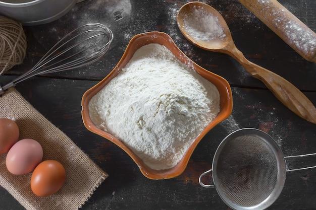 Weizenmehl in einer keramikschale und hühnereier für die teigzubereitung