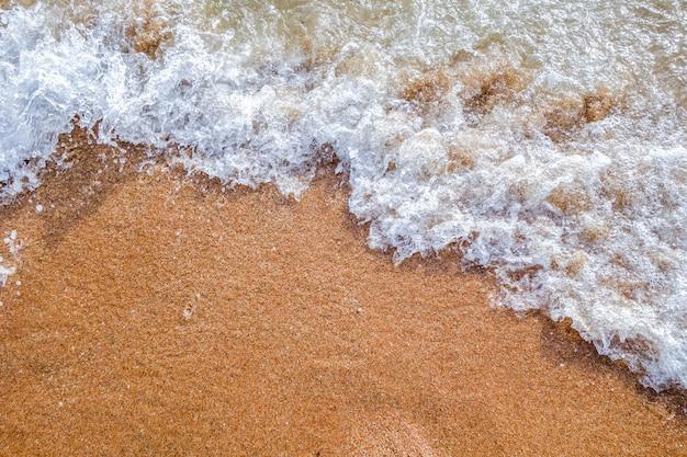 Welle auf sandozean-strandhintergrund