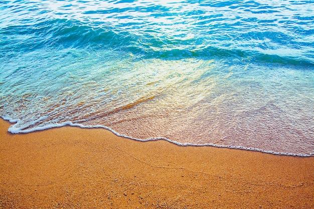 Welle des blauen ozeans am sandstrand. hintergrund.