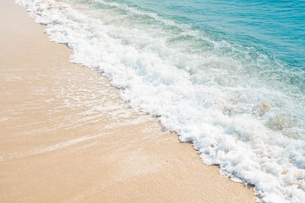 Welle des blauen ozeans am sandstrand. textur hintergrund.