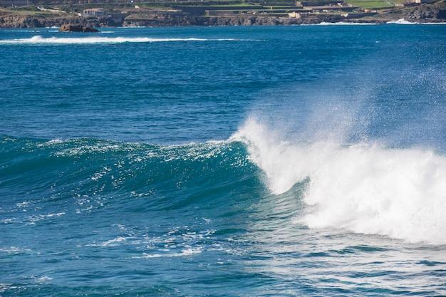 Welle, die den blauen ozean nahe der stadt einläuft.