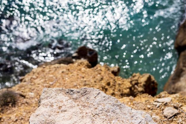 Welle, die gegen klippe, ansicht von oben bricht
