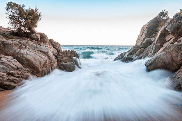 Welle kracht gegen die felsen am strand
