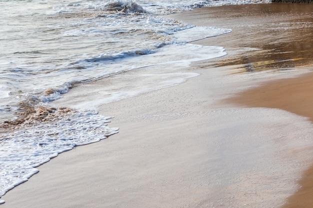 Wellen am strand an einem sonnigen tag und ruhigen see. schöne ocker-, braun-, blau- und weißtöne.