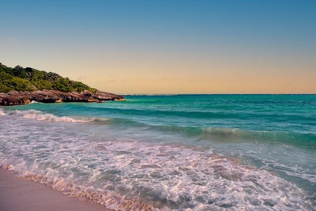 Wellen an einem weißen sandstrand mit türkisfarbenem wasser in puerto rico