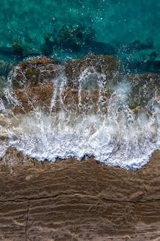 Wellen brechen auf braunen klippenfelsen bei steigender flut, drohnenperspektive direkt darüber