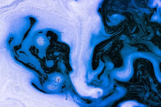 Wellen des schaums auf blauer flüssigkeit