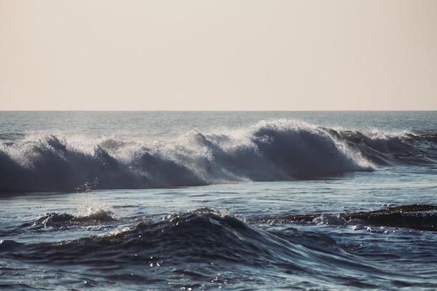 Wellen, die an der küste im tropischen meer im morgengrauen spritzen