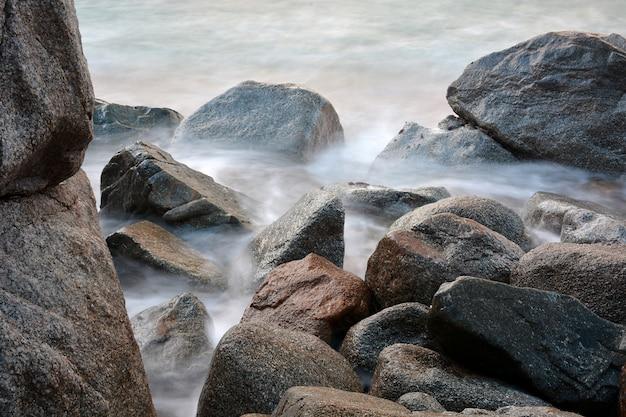 Wellen, die in die felsen des meeres in einem frühlingssonnenuntergang zusammenstoßen