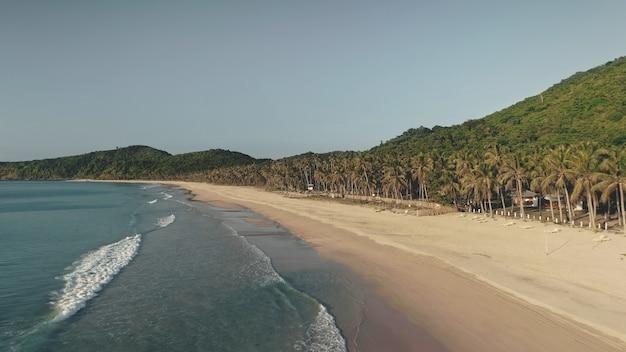 Wellen gewaschen sand ozean küste antenne. tropenwald auf der paradiesinsel. niemand tropische natur