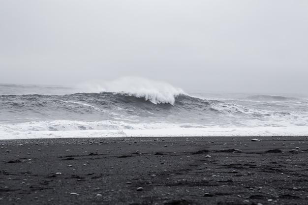 Wellen im schönen vulkanischen schwarzen sandstrand in island.